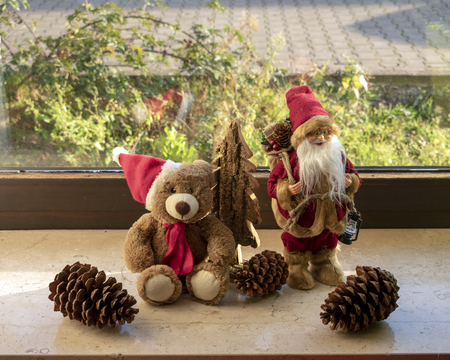 Christmas teddy and Santa Claus with decorations on the windowsill Standard-Bild - 117804149