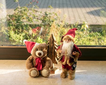 Christmas teddy and Santa Claus on the windowsill Standard-Bild - 117804150