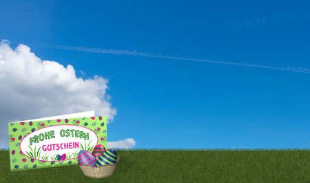 Gift card and easter basket on green meadow with blue sky. With text in german: Happy Easter and voucher. 3d rendering Standard-Bild - 120483783