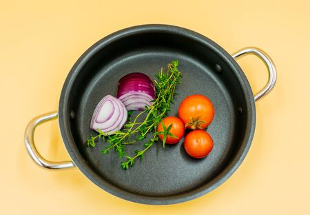 fresh tomatoes, onions and marjoram in the pan, view from above. Standard-Bild - 134139533