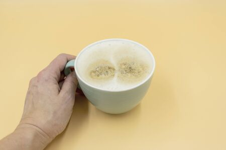 Hand holds coffee cup with whipped milk