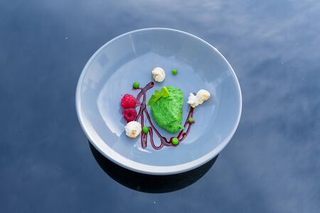 Pea and mint sorbet with raspberries and popcorn. View from above Standard-Bild - 134139596