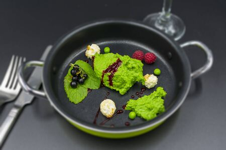 Pea sorbet with mint, berries and popcorn with blurred background. Standard-Bild - 134139600