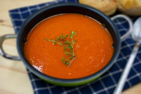 tasty tomato soup in rural style arranged in close-up.
