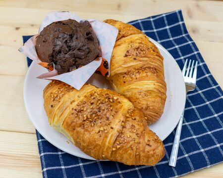 croissants with muffin on blue checkered napkin