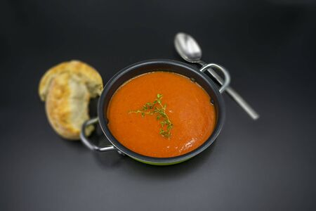 Mediterranean tomato soup with blurred background on black background.
