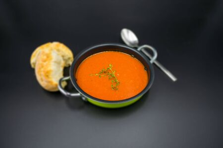 Mediterranean tomato soup simply presented on a black background.