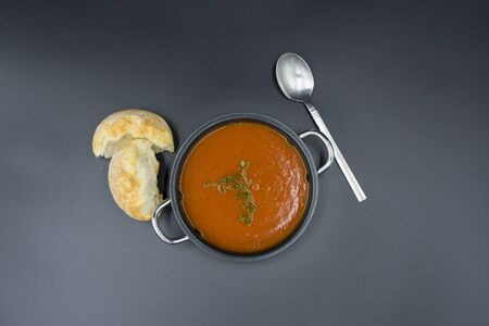 Mediterranean tomato soup simply presented on a black background, view from above. Standard-Bild - 132639072