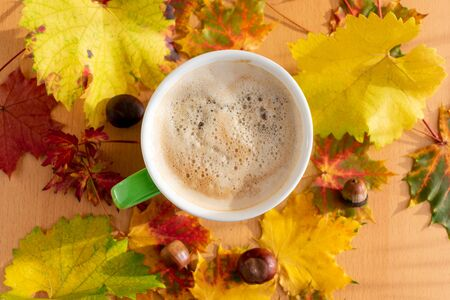 Cappuccino with autumnal decorations of leaves, acorns, chestnuts on wood, top view. Stockfoto