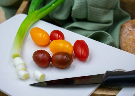 different varieties of mini tomatoes and freshly cut spring onion Banco de Imagens