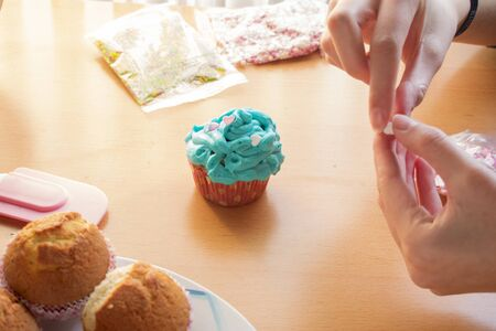 Hands decorating a homemade cupcake with hearts