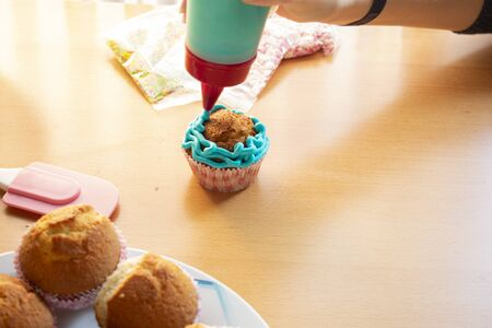 Apply blue cream to a homemade cupcake