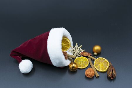 Santa hat with Christmas decorations made of cinnamon sticks, dried orange slices and Christmas tree ornaments on dark background Standard-Bild - 134139604