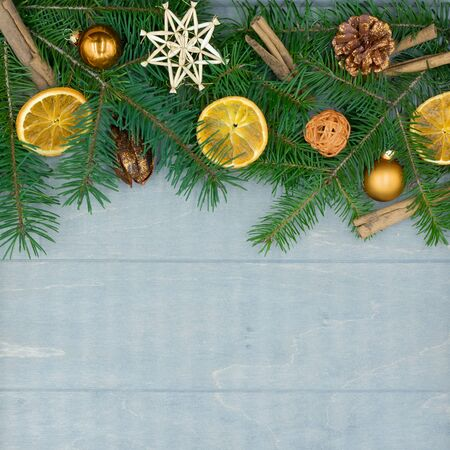 Christmas decorations of fir branches, dried oranges and cinnamon sticks on wood with copy space Standard-Bild - 134193930