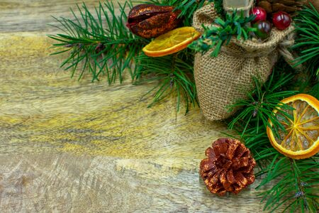 Wooden board with fir branches, dried oranges, cinnamon sticks and copy space in closeup Standard-Bild - 134193932