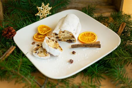 Baked apple stollen on white plate between Christmas decorations Standard-Bild - 134193939