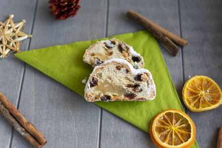 Christmas stollen with baked apple on green napkin with Christmas decorations Standard-Bild - 134193942