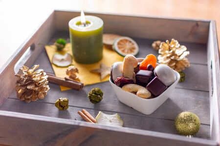 Small bowl of Christmas cookies on a wooden tray with burning candle and Christmas decorations Standard-Bild - 135649852