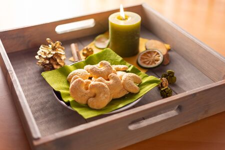Plate of vanilla crescents on a wooden tray with candle and Christmas decorations in the back light. Standard-Bild - 135649887