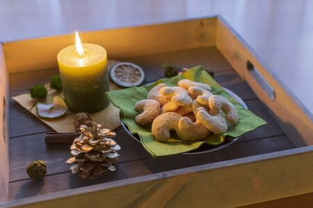 Plate of delicious vanilla crescents on a wooden tray by candlelight Standard-Bild - 135649854