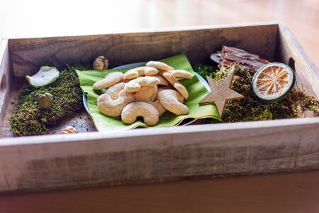 Plate of vanilla crescents on a wooden tray between decoration of moss Standard-Bild - 135649855