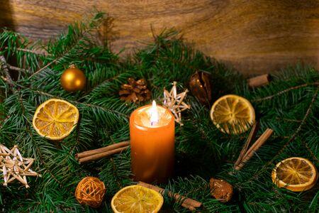 Christmas arrangement with burning candle in closeup Standard-Bild - 135649872