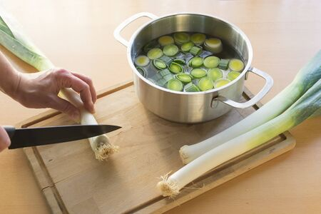 Hand holds leek for cutting with a knife. Sliced leek in pot with water next to it. Standard-Bild - 135649898
