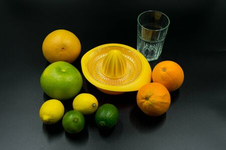 yellow citrus juicer with oranges, grapefruit, limes, lemons and empty glass on black background. Standard-Bild - 135196866
