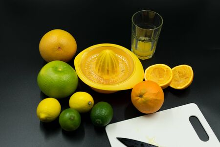 use juicer different citrus fruits, squeezed orange and cutting board with knife on black background. Standard-Bild - 135196780