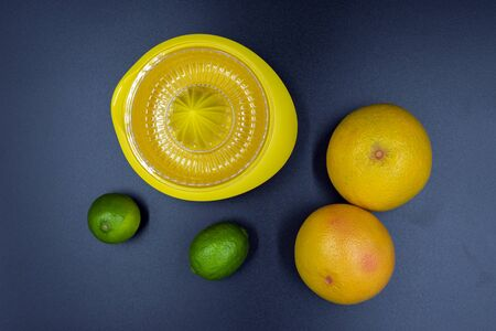 Citrus press with limes and grapefruits on blue background. View from above Standard-Bild - 135197110
