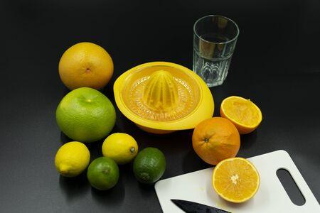 use juicer of various citrus fruits, sliced orange and squeezed orange on black background. Standard-Bild - 135196898