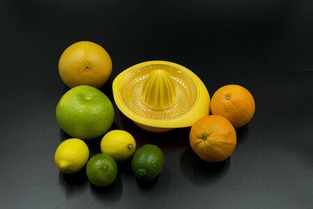 yellow citrus juicer with oranges, grapefruit, limes and lemons on black background. Standard-Bild - 135197134