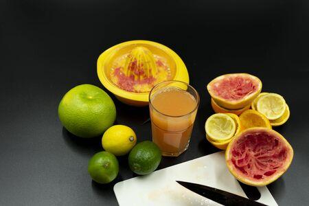 Homemade vitamin juice beside fruits and used juicer. On black background Standard-Bild - 135196941