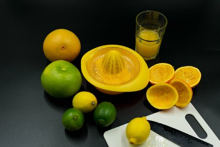 used orange squeezer with different fruits, orange peel and glass. On black background Standard-Bild - 135197090