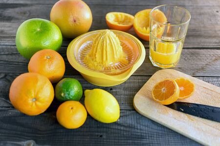 halved mandarin with various citrus fruits and juicer, cutting board, knife and juice glass. On wooden floor Standard-Bild - 135197194