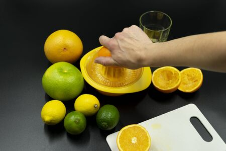 Orange press with different fruits. A hand just squeezes out an orange. Standard-Bild - 135197182