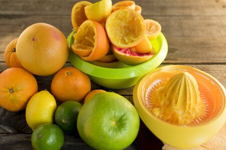 Citrus fruits with use of juicers and squeezed fruit bowls. On wooden floor Standard-Bild - 135197123