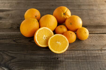 Halved orange with whole oranges and mandarins on a wooden background. Standard-Bild - 135197026