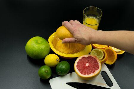 Hand squeezes grapefruit in juicer. On black background Standard-Bild - 135196917