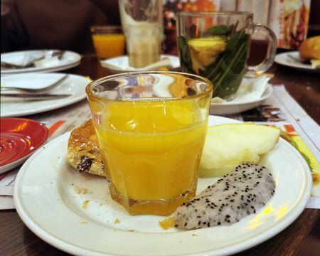 Breakfast table in the café with fresh orange juice, fruit, chocolate rolls and tea Standard-Bild - 136354672