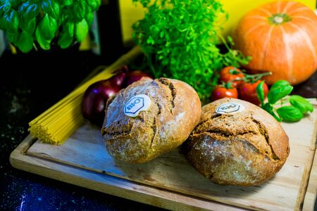 Organic bread on a wooden board with herbs and vegetables as decoration. High contrast Standard-Bild - 136354642