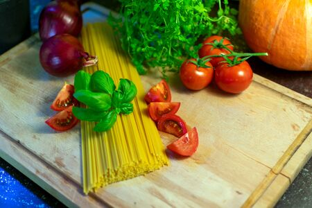 raw spaghetti with decorations of tomatoes, onions and basil on a wooden board. Standard-Bild - 136354603