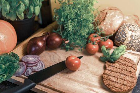 Ingredients for a vegetarian hamburger on a wooden board. Standard-Bild - 136939316