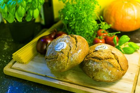 Organic bread on a wooden board with herbs and vegetables as decoration. Standard-Bild - 136354725