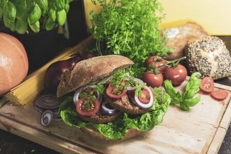 tasty vegetarian burger in rye bun with tomatoes and onions on a wooden board Standard-Bild - 136940535