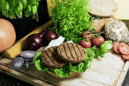 Organic bread rolls with salad and vegetarian burger on a wooden board