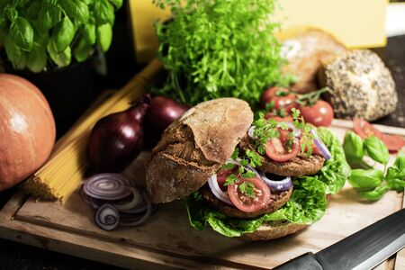 vegetarian organic burger in rye bun with tomatoes and onions on a wooden board