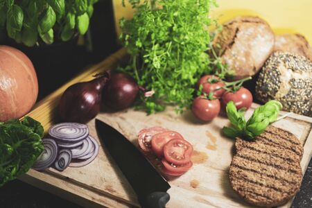 Ingredients for a vegetarian burger on a wooden board. In the center are sliced tomato slices with a knife Standard-Bild - 136354654