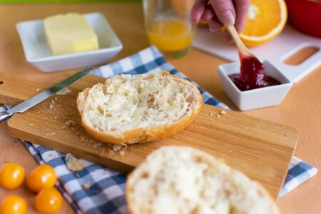Breakfast table with half rolls with butter and a hand that dips into the jam with a spoon. Standard-Bild - 136940541