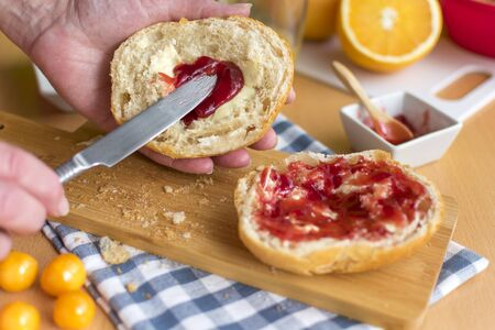 Woman's hands spread half a bun with jam